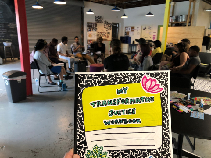 "A hand holding a hand-drawn composition notebook with the title ""My Transformative Justice Workbook"" in the foreground, with a group of training participants in the background."